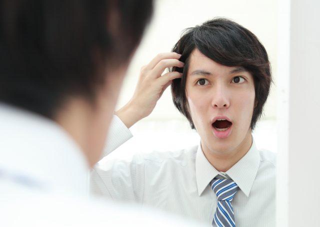 鏡を見て薄毛を心配する男性