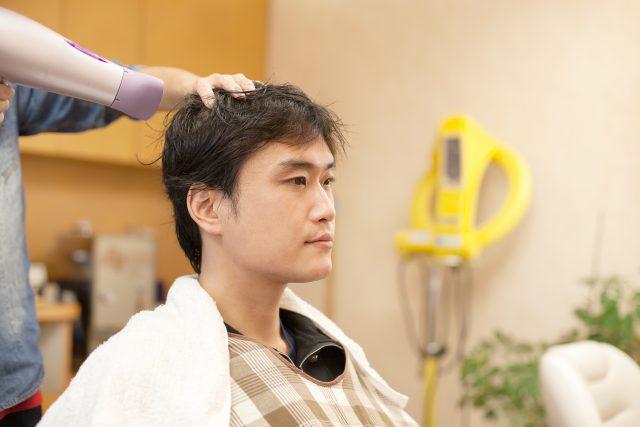 理髪店で髪の毛を乾燥してもらう男性