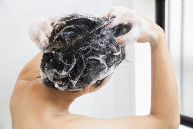 バスルームで頭を洗う男性